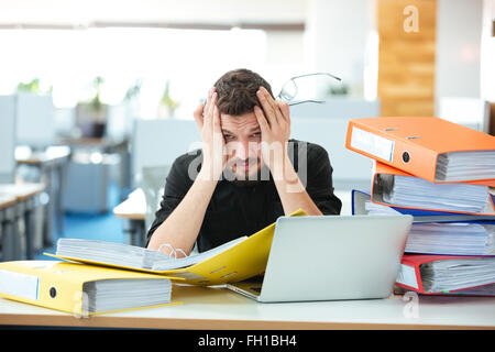 Tired businessman working with papers in office - Stock Photo