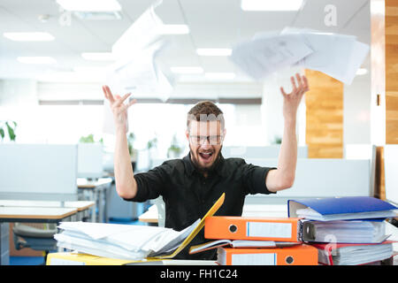 Angry businessman sitting at the table and shouting in office - Stock Photo