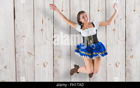 Composite image of pretty oktoberfest girl smiling and jumping - Stock Photo