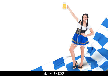 Composite image of pretty oktoberfest girl holding beer tankard - Stock Photo