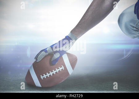 Composite image of cropped image of american football player placing ball - Stock Photo