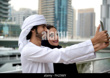 Young Emirati arab couple taking selfie with smartphone - Stock Photo