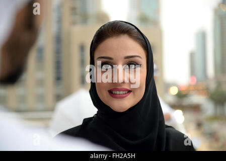 Young Emirati arab couple talking by the canal - Stock Photo