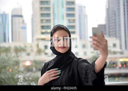 Young beautiful Emirati arab woman taking selfie with her smartphone - Stock Photo