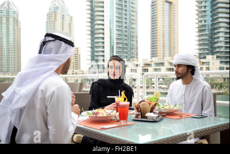 Young Emirati arab friends dining in a restaurant - Stock Photo