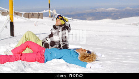 Couple resting on hill after skiing - Stock Photo