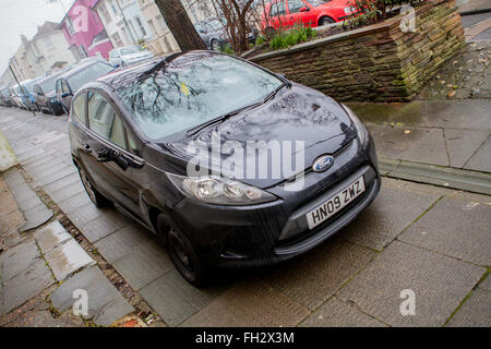 Car illegally parked on the pavement - Stock Photo