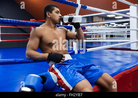 Male boxer leaning on boxing ring and drinking water - Stock Photo