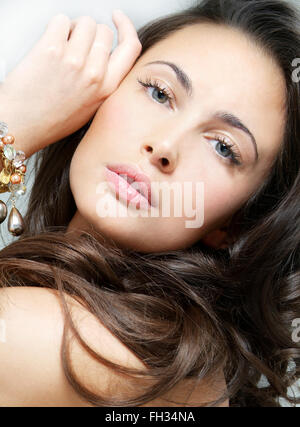 Studio portrait of a beautiful young woman with auburn hair and wearing a bracelet. - Stock Photo