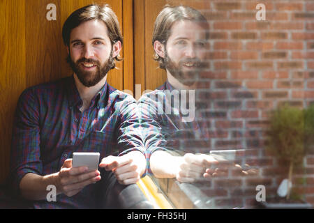 Hipster student sending text in canteen - Stock Photo