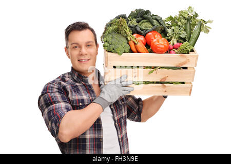 Young male farmer carrying a wooden crate full of fresh vegetables isolated on white background - Stock Photo