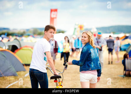 Teenage couple with bike at summer music festival - Stock Photo