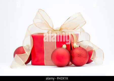 A red Christmas present with gold ribbon and red tree decorations isolated on a white background. - Stock Photo