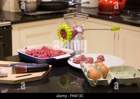 Home kitchen where meat is being chopped, minced or ground to make Italian style meatballs - Stock Photo