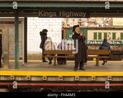 Orthodox Jewish man takes photo while waiting for a B Train at Kings Highway elevated subway station in Brooklyn, - Stock Photo