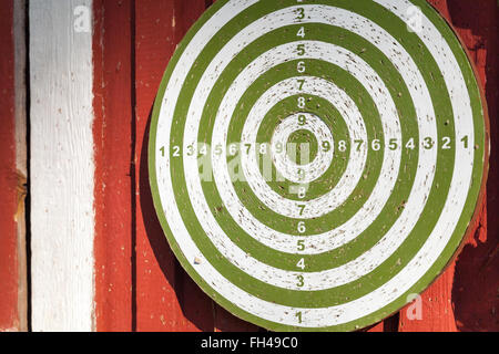 Old darts target hanging on red wooden wall - Stock Photo