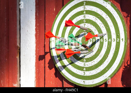 Darts target with many arrows hanging on red wooden wall - Stock Photo
