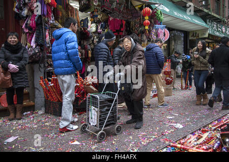 Older woman shopping along Mott St. during Chinese New Year in New York City. - Stock Photo