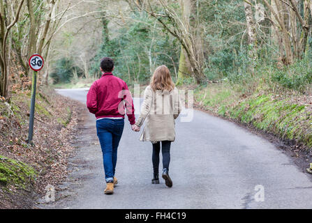 Young couple walk away hand in hand along a tree lined country lane in early Spring, Surrey, England. - Stock Photo