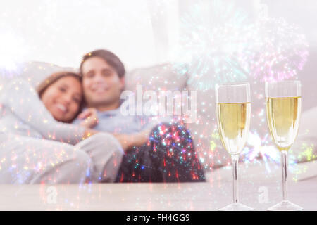 Composite image of couple resting on a couch with flutes of champagne - Stock Photo