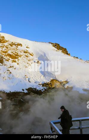 Krýsuvík geothermal area boiling hot spring where tourist on boardwalk engulfed in steam winter Reykjanes Peninsula - Stock Photo
