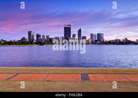 panoramic view of skyscrapers in Perth, Western Australia, across Swan river at sunrise. Walking trail in background. - Stock Photo