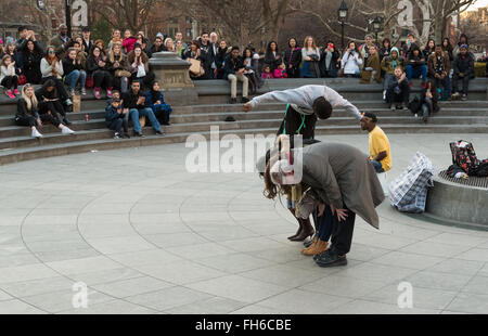 Street performance in Washington Square Park of acrobat somersaulting over volunteers with crowds of spectators - Stock Photo