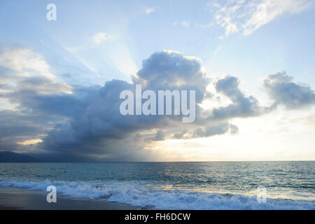 Sun ray clouds is lit brightly light golden seascape with waves rolling to the shore as scattered sunbeam break - Stock Photo