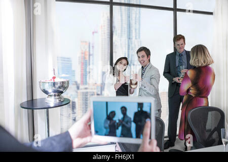 Successful business people having a work party, man taking picture with digital tablet - Stock Photo