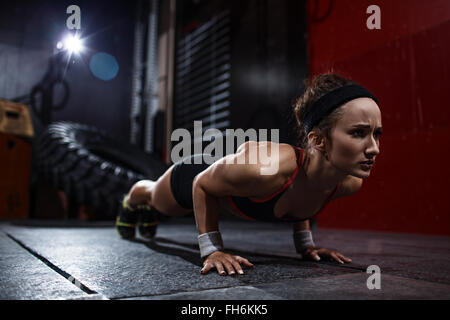 Fit woman doing push-ups in gym - Stock Photo