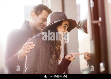 Young couple looking in shop window - Stock Photo