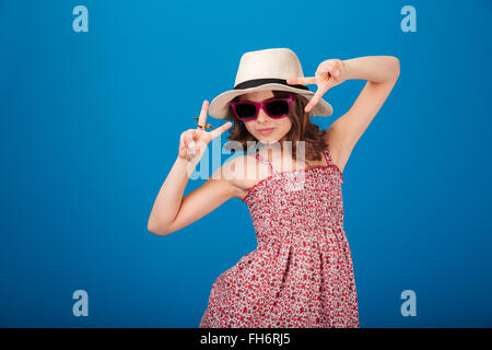 Cute playful little girl in hat, sundress and sunglasses showing victory sign with both hands over blue background - Stock Photo