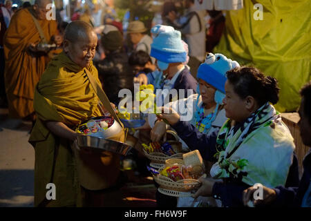 Buddhist monks receiving alms from local people before first light on Chaikhong street, which on weekend evenings - Stock Photo