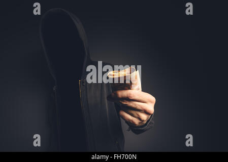 Unrecognizable hooded computer hacker offering cash money, cyber crime, blackmail and extortion concept. - Stock Photo