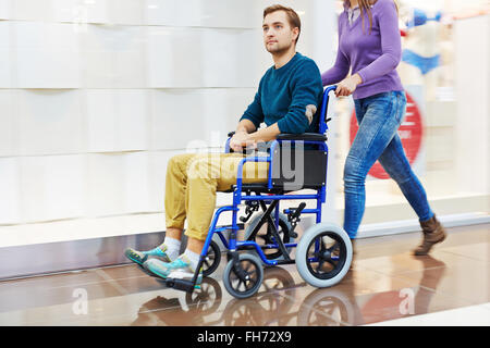 Guy in wheelchair being moved by his caregiver - Stock Photo