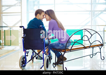 Amorous girl sitting on bench close to her boyfriend in wheelchair - Stock Photo