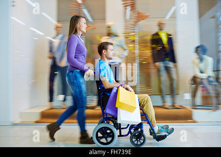 Pretty girl shopping with her disable boyfriend in wheelchair - Stock Photo