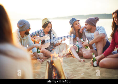 Happy friends with drinks sitting on sand around campfire - Stock Photo