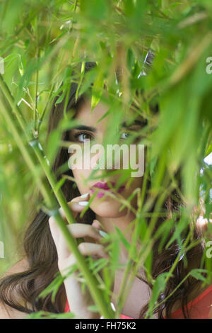 Scared young woman hiding behind trees - Stock Photo