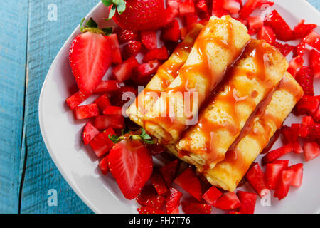 rolled pancakes with strawberries and caramel breakfast - Stock Photo