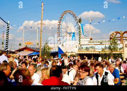 People enjoying nice weather in beer garten at the Oktoberfest in Munich - Stock Photo