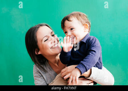 Portrait of happy mother with her little son in front of green background - Stock Photo
