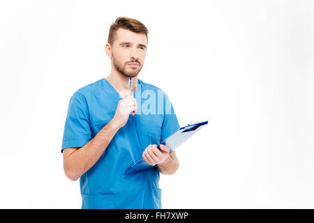 Pensive male doctor standing with clipboard isolated on a white background - Stock Photo