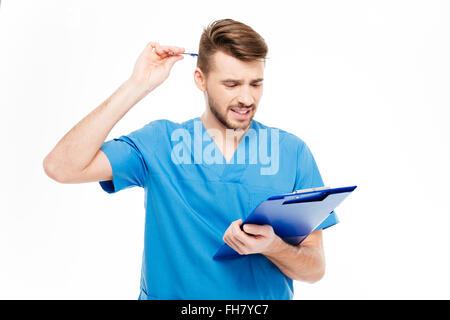 Thoughtful male doctor standing with clipboard isolated on a white background - Stock Photo