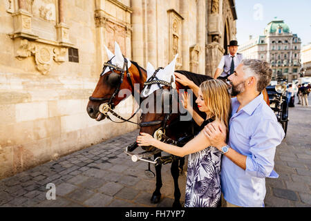 Austria, Vienna, couple stroking horse in front of St. Stephen's Cathedral - Stock Photo