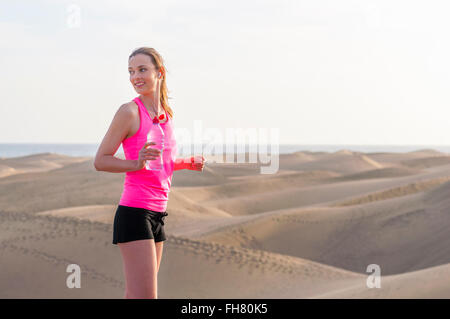 Young woman jogging on the beach, taking a break - Stock Photo