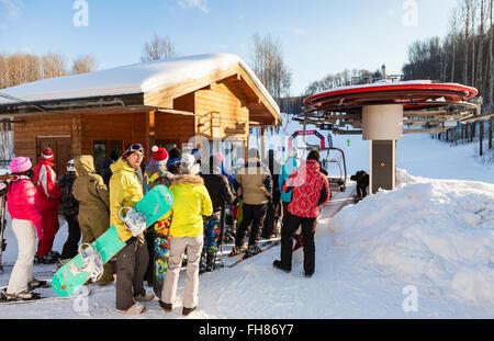 People stand in line on сhairlift in 'Krasnaya Glinka' mountain ski resort in winter