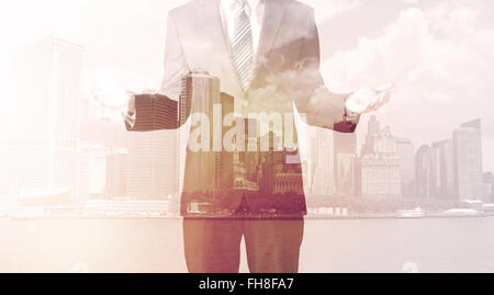Businessman standing at cityscape background - Stock Photo