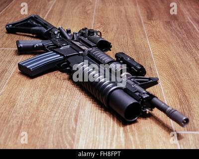 AR15 rifle with grenade launcher on the wooden floor, selective focus - Stock Photo