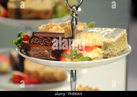 Fancy cakes on a cake stand at a buffet. Selective focus with good separation of depth. - Stock Photo